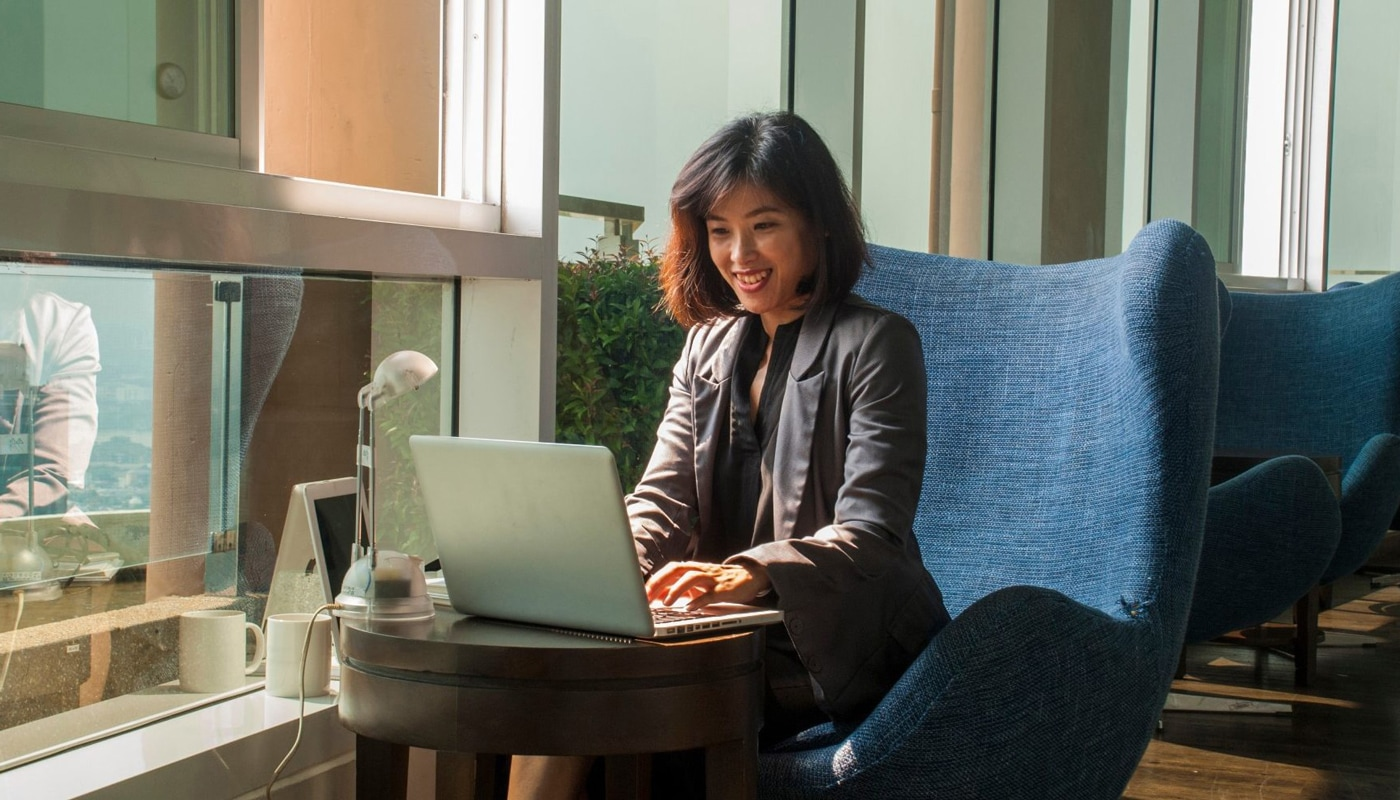 Businesswoman smiling while working with a laptop and a lamp placed beside her in the office